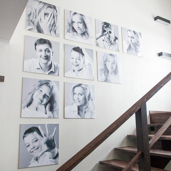семейные фотографии одинакового размера на стене лестницы