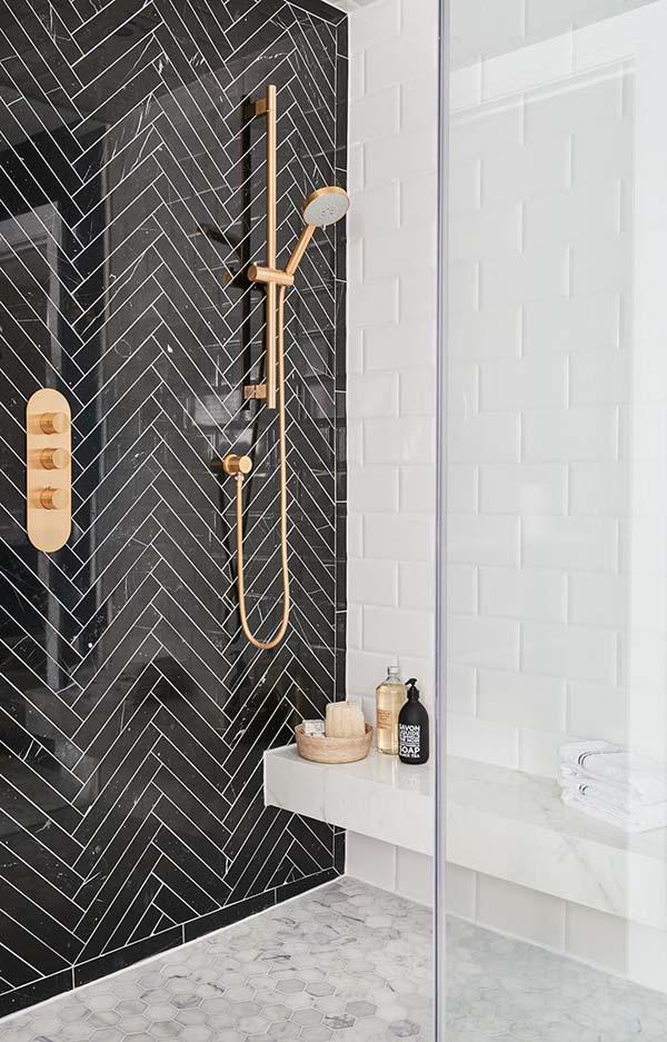 стена в ванной отделана черной плиткой с укладкой елочкой