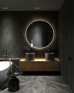 круглое зеркало на черной стене в ванной