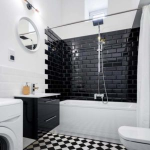 черная плитка на одной стене в ванной
